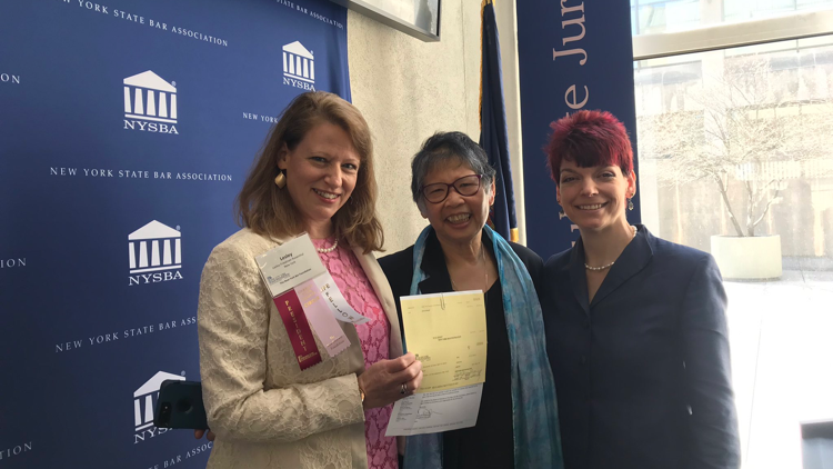 image of President Lesley Rosenthal presenting grant check to Lillian Moy, Executive Director of the Legal Aid Society of Northeastern New York, with staff member Victoria Esposito
