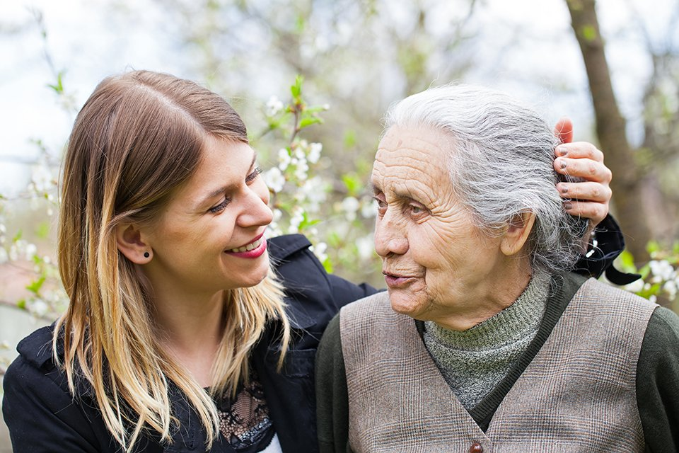 image of young woman smiling at elderly woman, speaking to one another