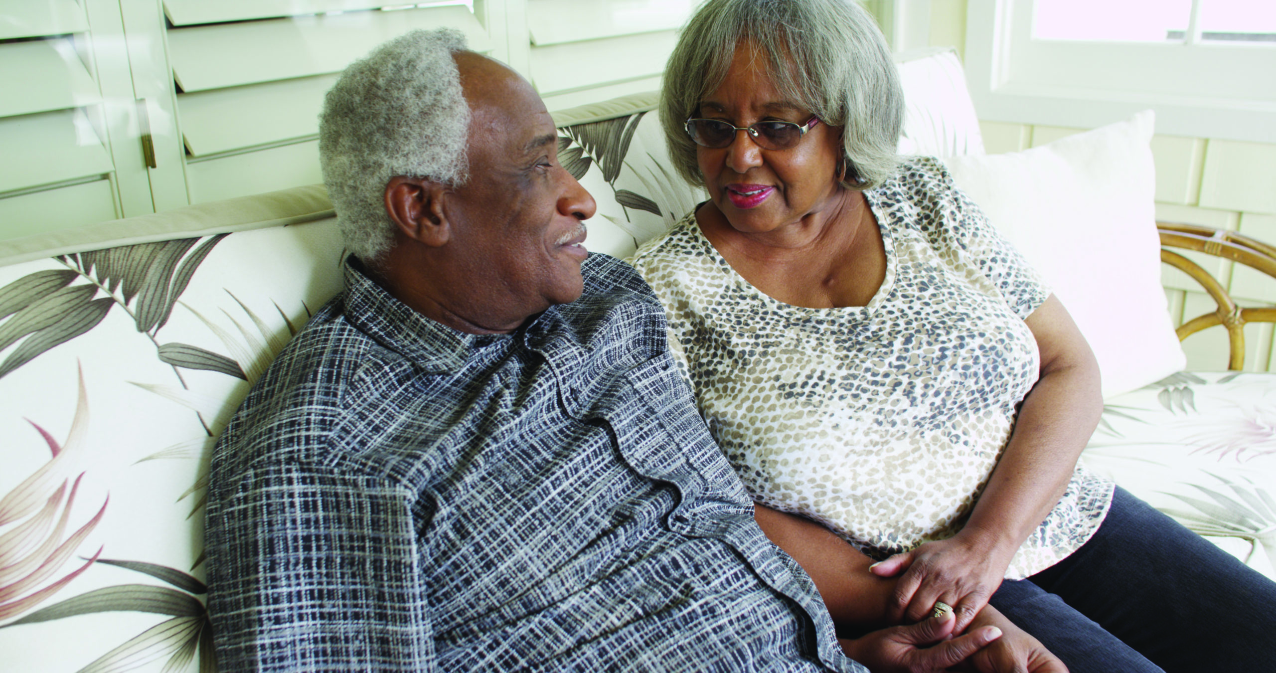 image of elderly couple holding hands, sitting on couch