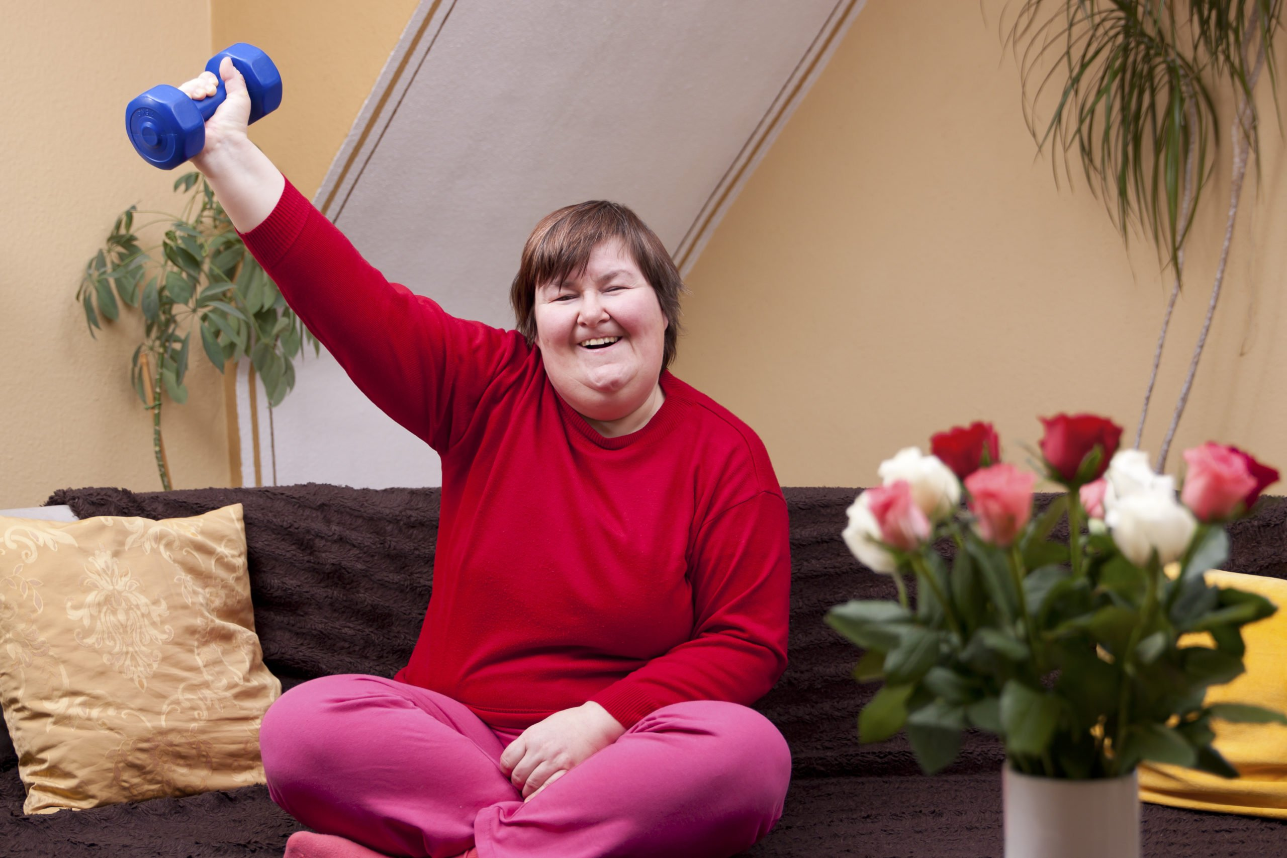 image of smiling woman with down syndrome lifting hand held weight