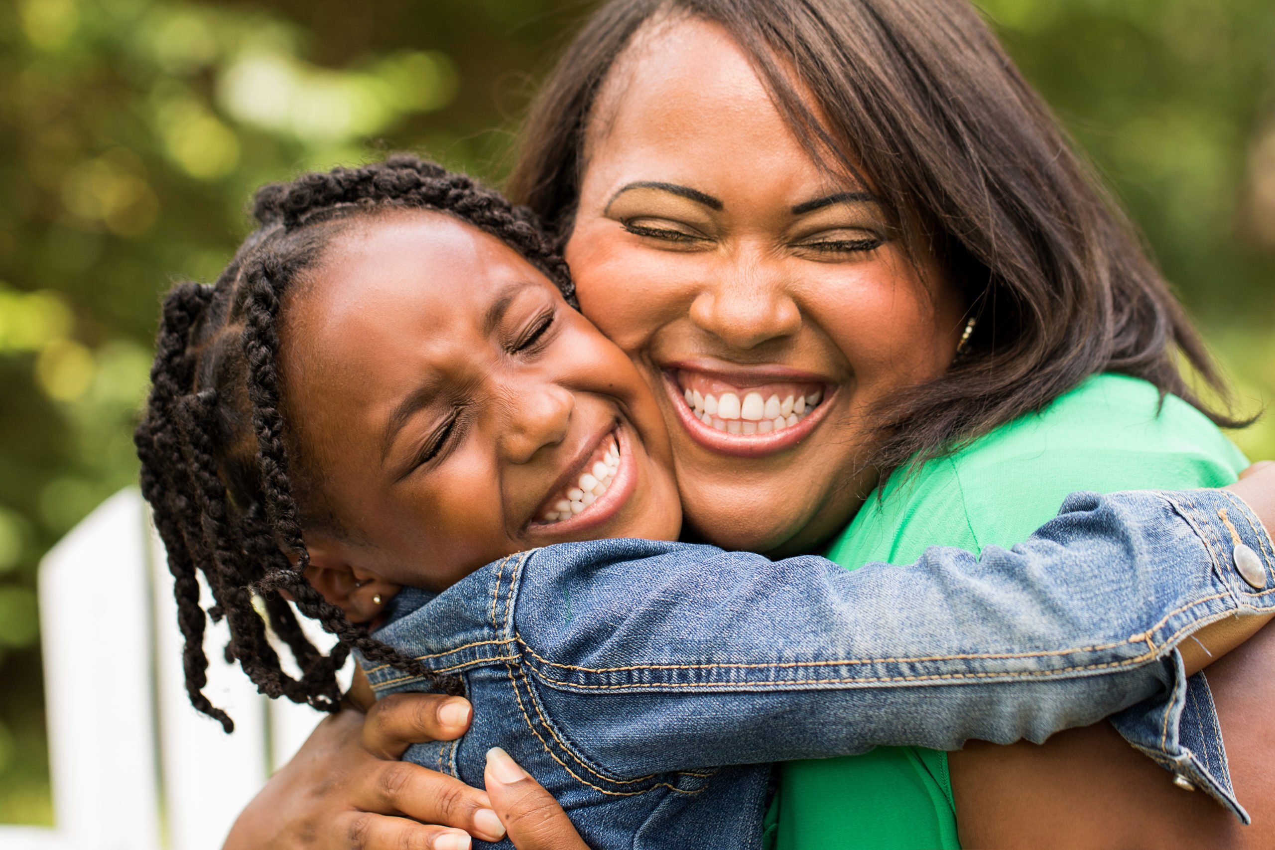 image of woman hugging young girl tightly, both smiling