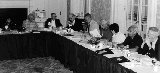 several people sitting at a table in a board meeting