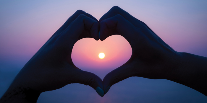 heart hands with sunset in the background